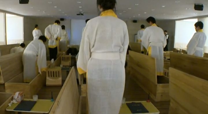 Program participants prepare to enter their caskets at the Hyowon Healing Center. They will stay in these coffins for 10 minu