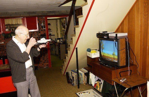 Baer playing a video game he invented; his basement workshop is in the background.