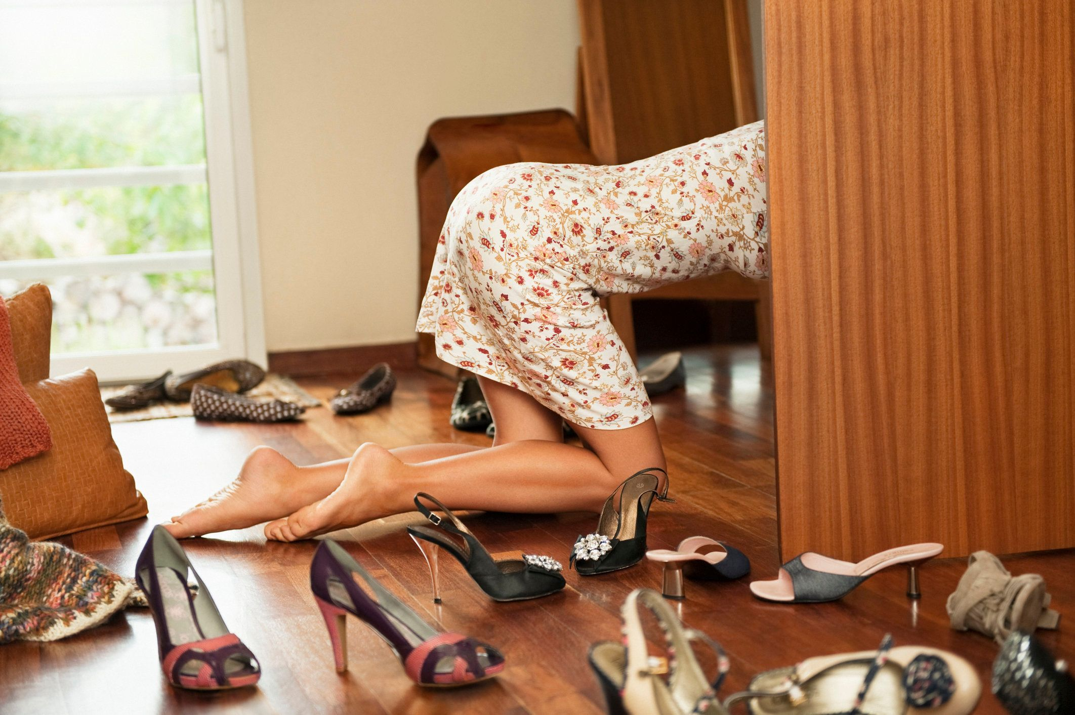 Young woman with a light flowered short dress kneeling barefoot on a hardwood floor among many shoes, she is searching for shoes and entering into her locker opened half hiding her, empty space on right side, wide angle view, France, Alpes Maritimes, Nice