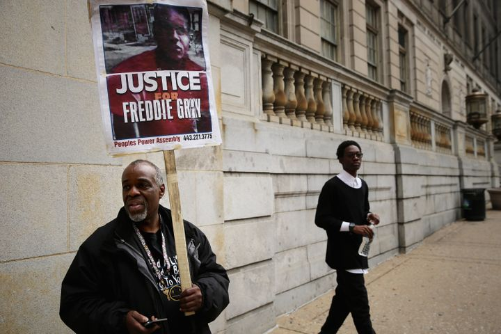 Demonstrators Arthur Johnson Jr. (L) and Shai Vaughn stand outside the Baltimore City Circut Courthouse East during the trial