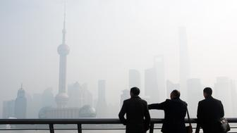 Men stand along the Bund in front of the financial district of Pudong, obscured by heavy pollution, in Shanghai on December 15, 2015.  According to local reports on December 14, Shanghai's environmental authority launched emergency measures against pollution after lingering smog was forecasted. The chronic haze blanketing northeastern China earlier this month was so thick that, unlike the Great Wall, it could be seen from outer space, according to satellite photographs from NASA.      AFP PHOTO / JOHANNES EISELE / AFP / JOHANNES EISELE        (Photo credit should read JOHANNES EISELE/AFP/Getty Images)