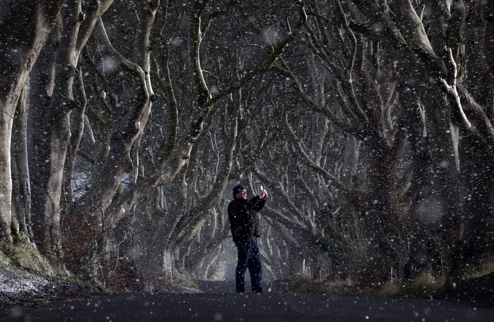 "A man takes a picture with his cell phone through heavy snow at the <a href=""https://www.huffpost.com/entry/irelands-dark-hed"