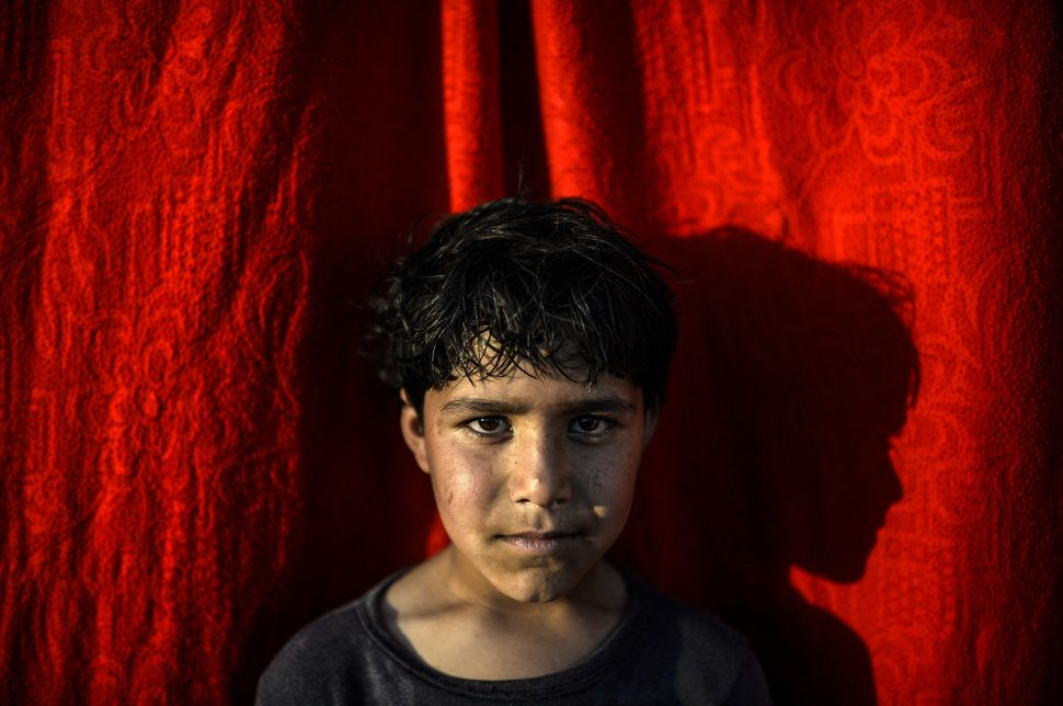 Arif,&nbsp;a 10-year-old Syrian Kurdish refugee, poses at the Rojava refugee camp in Sanliurfa, Turkey, on Feb. 1. As the <a