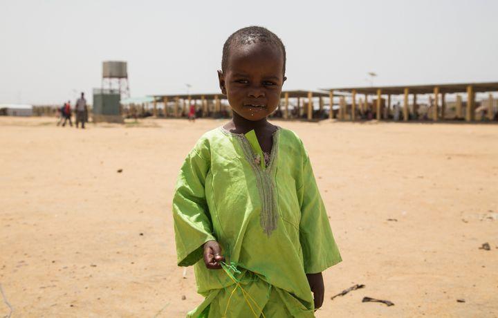 A Chadian kid holds bottle taps at a slumdog of N'djamena, Chad on June 22, 2015.