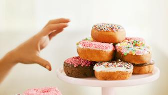 Woman reaches for a donut sitting on a white stand on the wood table in front of her. Another tower of donuts is visible in the foreground.