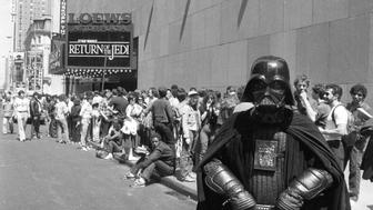 """""""Star Wars"""" fan Danny Fitzgerald of Staten Island, in Darth Vader costume, poses in front of Loews Astor Plaza movie theater in Times Square in New York, May 25, 1983, where fans are lined up for the premiere of """"The Return of the Jedi,"""" the third in a series of the """"Star Wars"""" saga.  (AP Photo/Dave Pickoff)"""