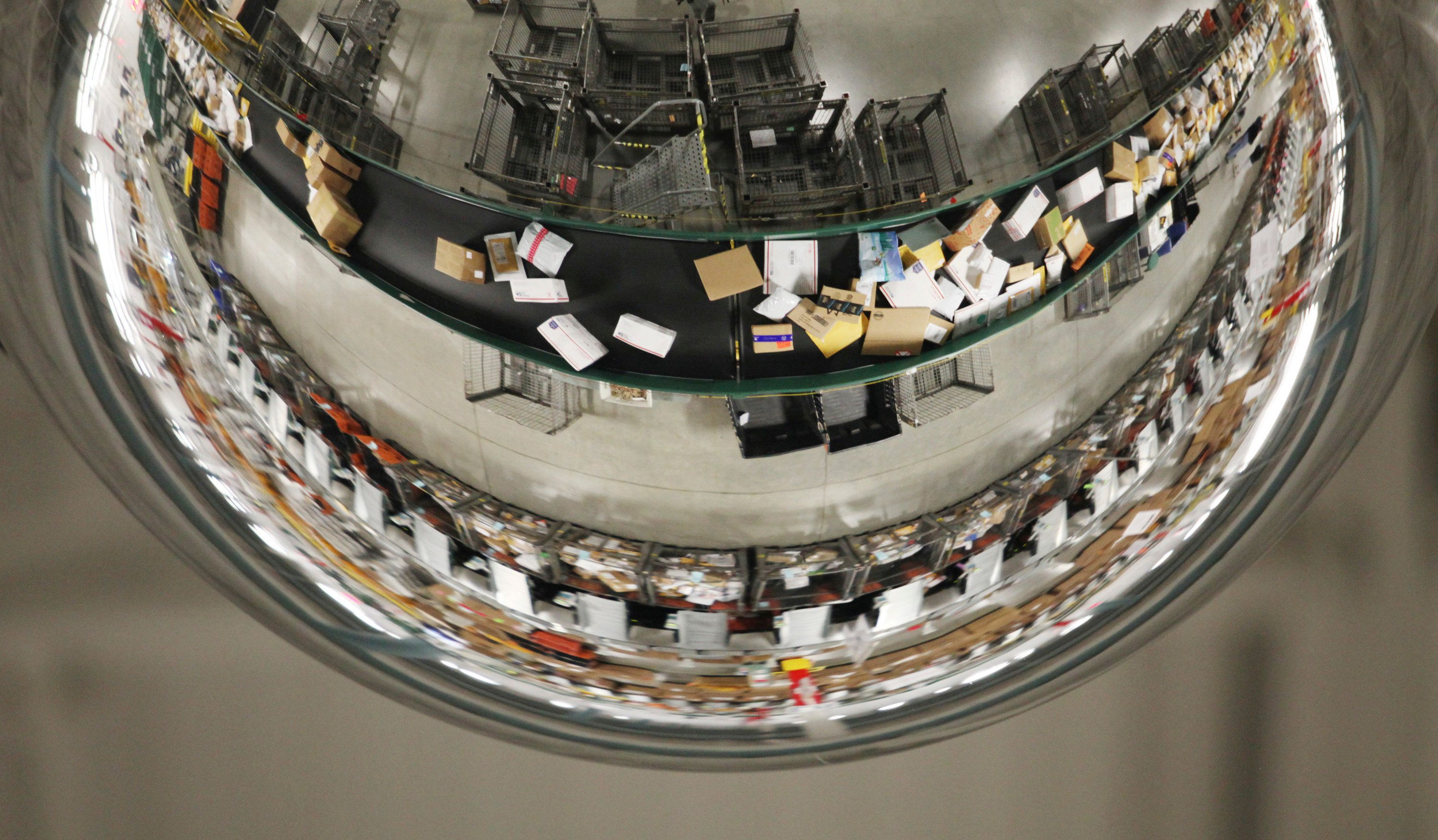SCARBOROUGH, ME - DECEMBER 18: A domed mirror reflects packages moving along a conveyor belt Thursday, Dec. 18, 2014 at the USPS sorting facility in Scarborough, Maine. The mirror allows for workers to see that the belt is functioning properly and there are no packages jammed. (Photo by Joel Page/Portland Press Herald via Getty Images)