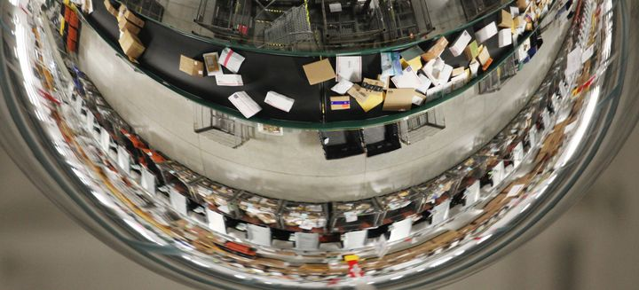 A mirror reflects packages moving along a conveyor belt at aUSPS sorting facility in Scarborough, Maine. ThePosta