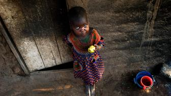 GALUFU, MALAWI - OCTOBER 16: Magreti Nangamtani, age 3, eats a mango outside the family house on October 16, 2005 in Galufu, Malawi. Her mother, Stelia, age 26, and little sister Pilirani, age 2, are one of the poorest families in Galufu, and they have to beg for food every day Magreti has climbed a tree to find a mango to eat as the family doesn't have any maize to cook porridge. Most people in the village are poor and hungry, and cannot afford to buy maize at the market. The price is twice as much as the government subsidized prices. The government used to sell subsidized maize and fertilizer but not anymore. Many in the village eat mangoes and even boil unripe ones, as they cannot afford to buy anything else. The harvest was very bad in 2005 and the next one, due in April 2006 is uncertain because of lack of rains and drought. The village has seen an increase in poverty the last few years due to drought and HIV/Aids. Southern Africa has been hit by a severe hunger crisis due to drought and poverty. An ever-increasing HIV/Aids rate adds to the misery. Malawi is one of the worst hit areas and Galufu village is a typical small village that has become victim of this poverty spiral.  (Photo by Per-Anders Pettersson/Getty Images)