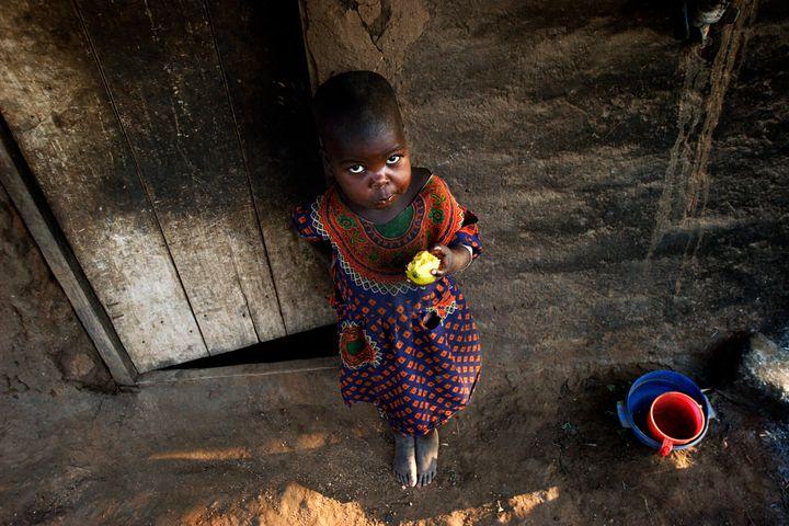 GALUFU, MALAWI - OCTOBER 16: Magreti Nangamtani, age 3, eats a mango outside the family house on October 16, 2005 in Galufu,