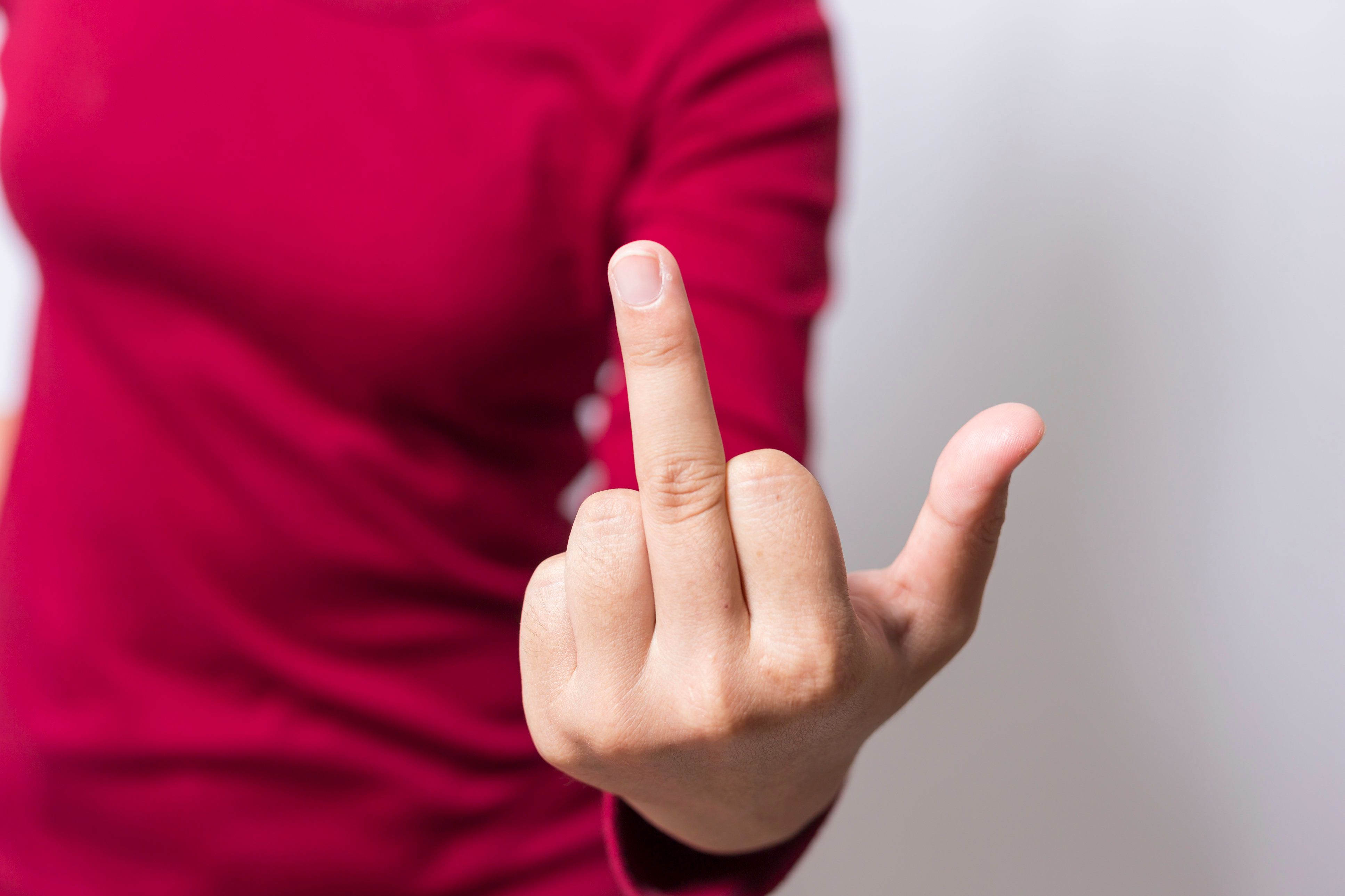 Bad woman is showing fuck off with the middle finger