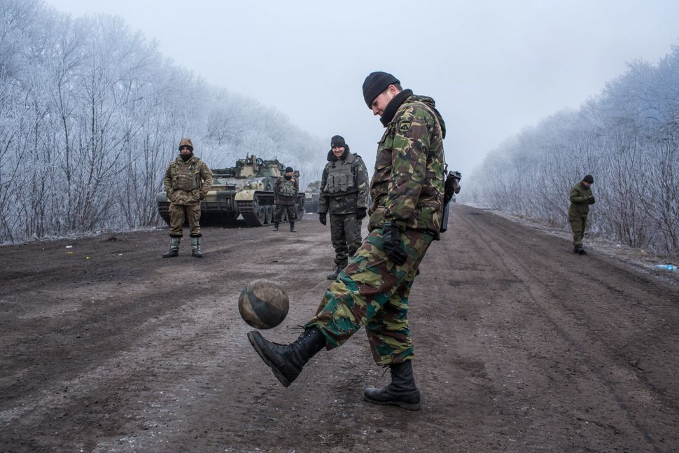 Ukrainian soldiers play football on a road leading to the embattled town of Debaltseve on Feb. 15. Tensions between Ukra