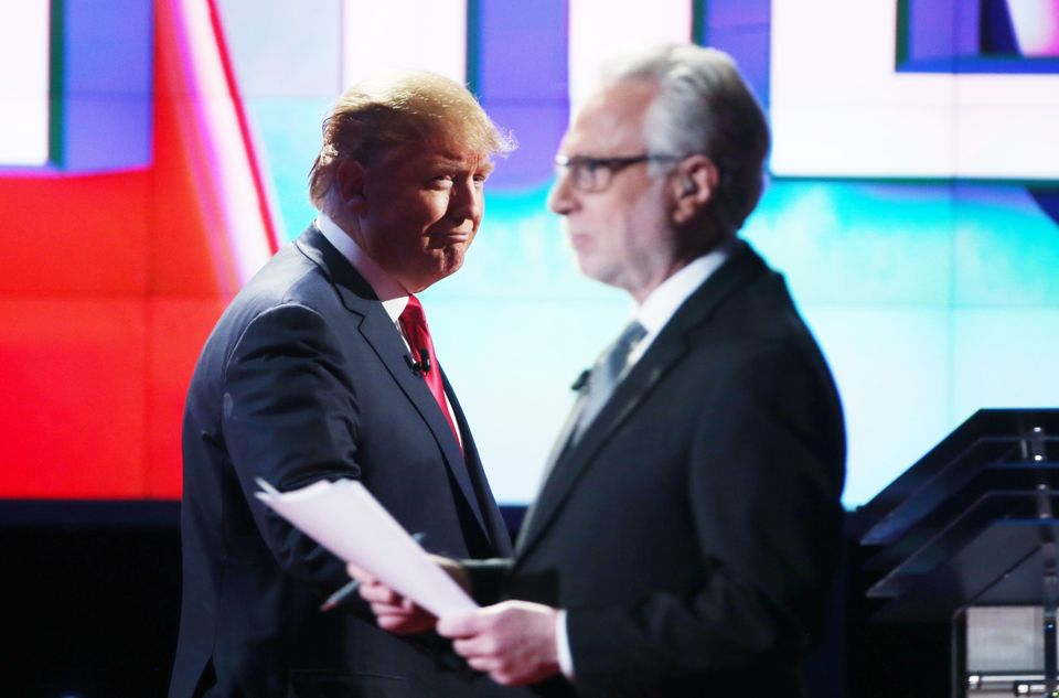 Republican presidential candidate Donald Trump walks onstage past CNN anchor Wolf Blitzer during the Republican presidential
