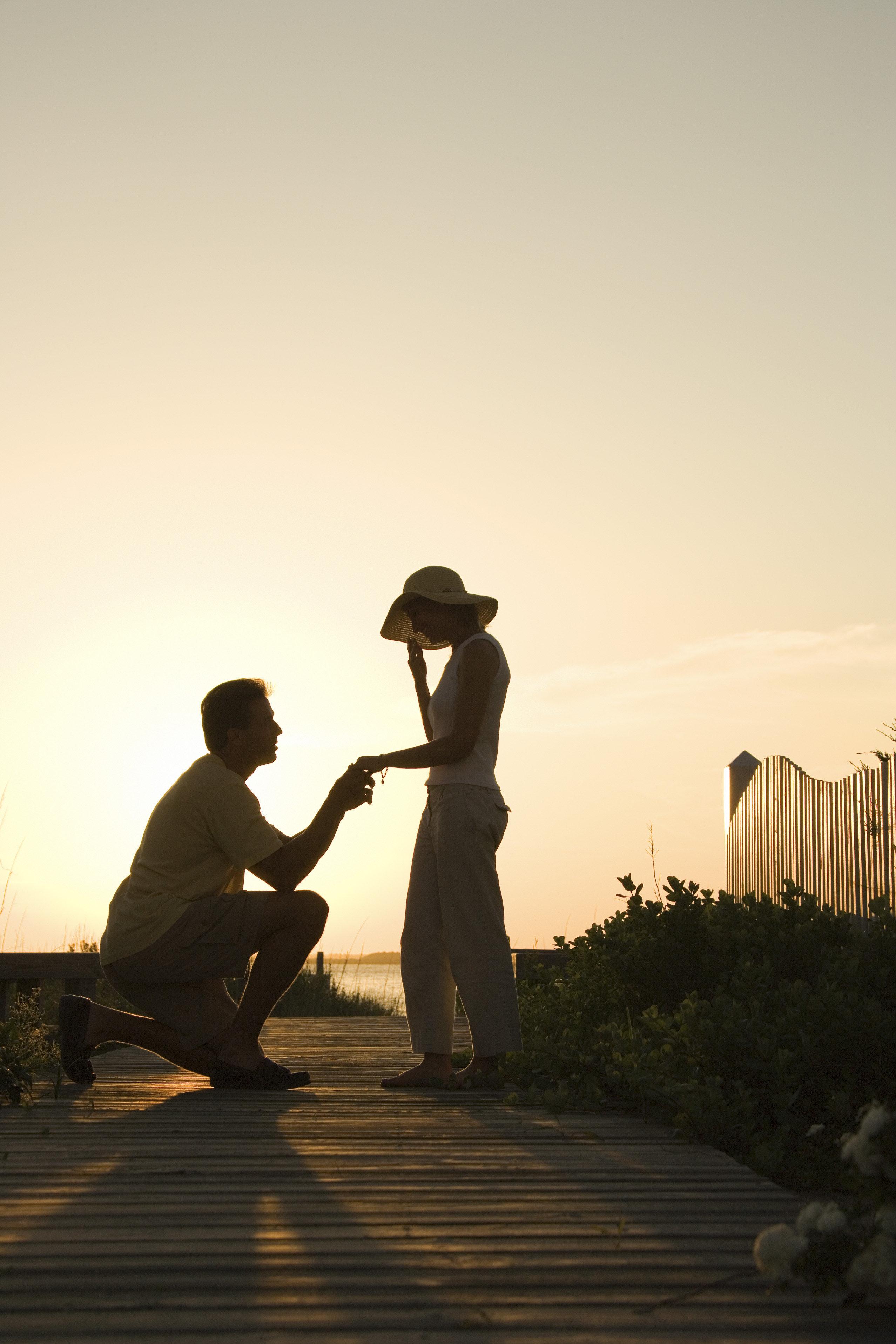 Silhouette of man proposing to woman on beach boardwalk