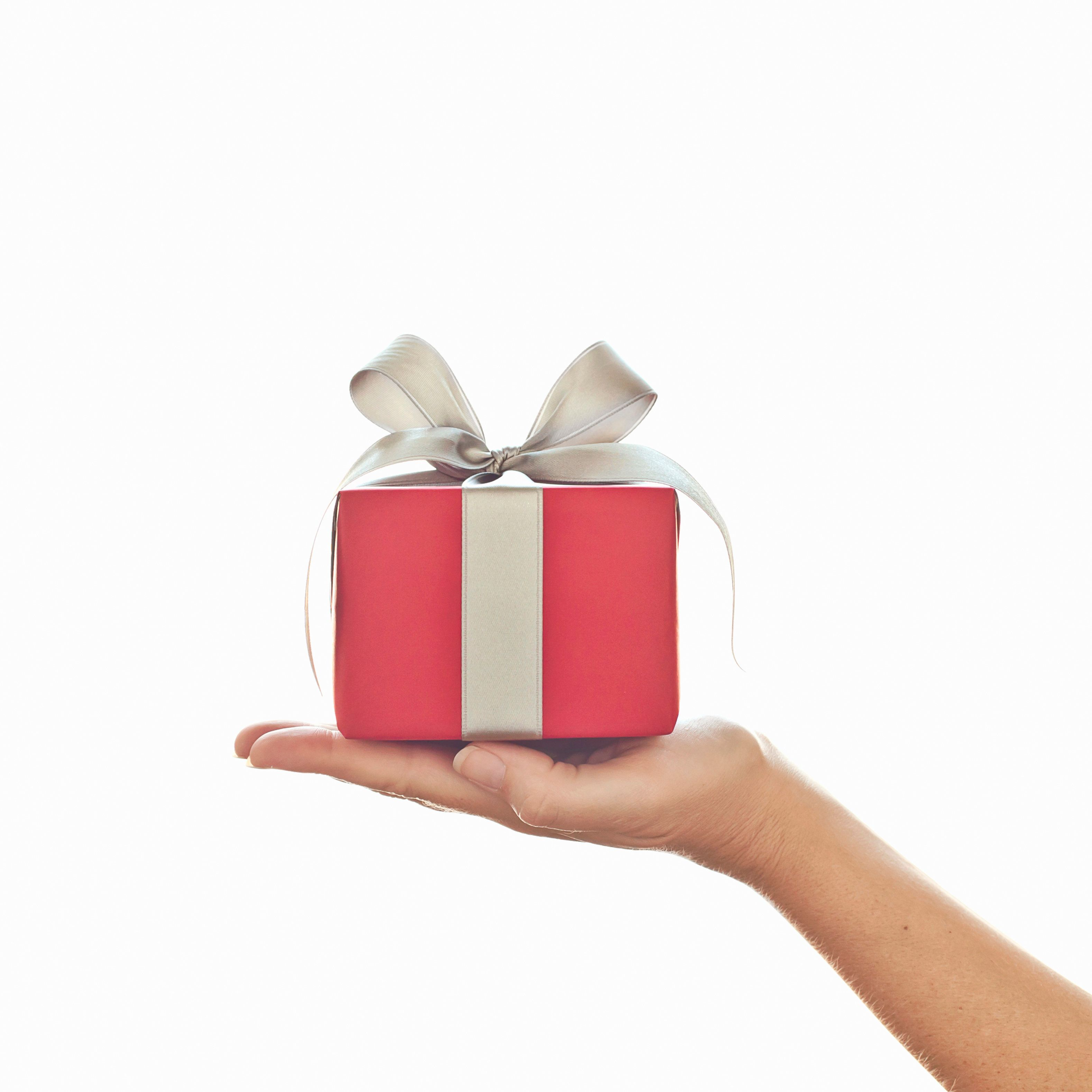 female hand holding red gift with silver bow