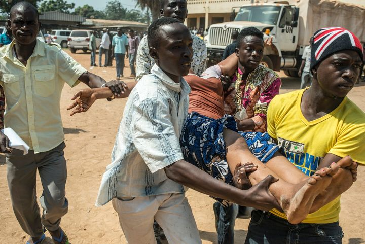 TOPSHOT - A group of men carry a woman who passed out as heavy gunfire is directed towards the Baya Dombia school where voter