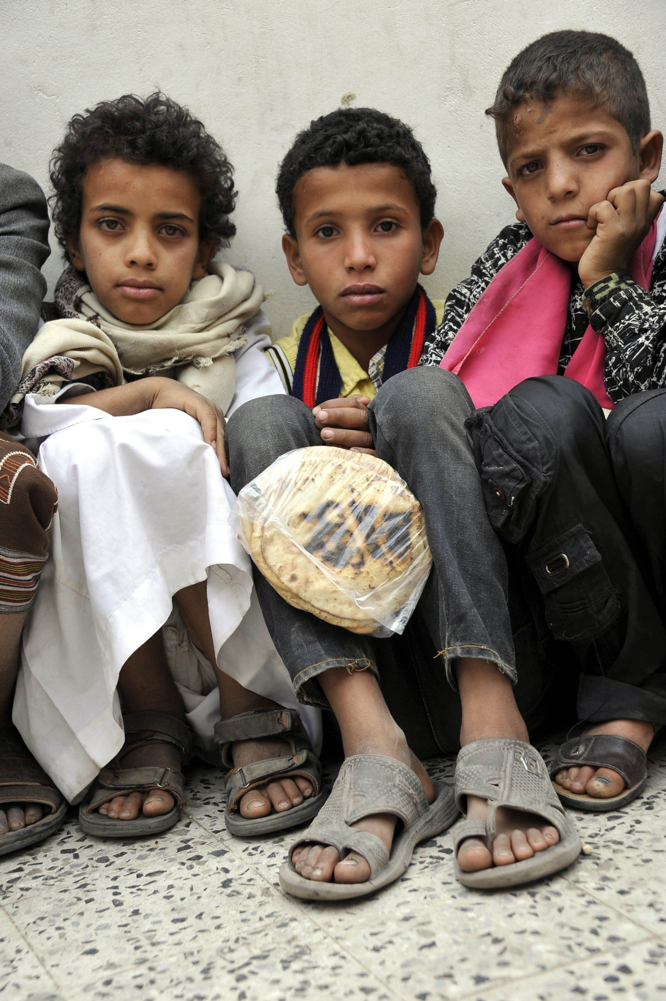 SANAA, YEMEN - JUNE 26: Yemenis wait in line at a school garden in Sumeyla district of capital Sanaa to receive food aids pro