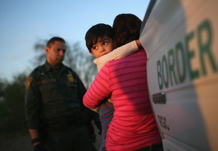A one-year-old from El Salvador clings to his mother after she turned themselves in to Border Patrol agents on December 7, 20