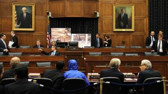 WASHINGTON, DC - JULY 31:  Syrian Army defector known as 'Caesar', in a blue hooded jacket, who provided 55,000 photographs that document the torture and killing of more than 10,000 detainees tortured and slained allegedly by the Assad regime in Syria, waits to brief the House Committee on Foreign Affairs in Washington, DC on July 31, 2014. (Photo by Erkan Avci/Anadolu Agency/Getty Images)