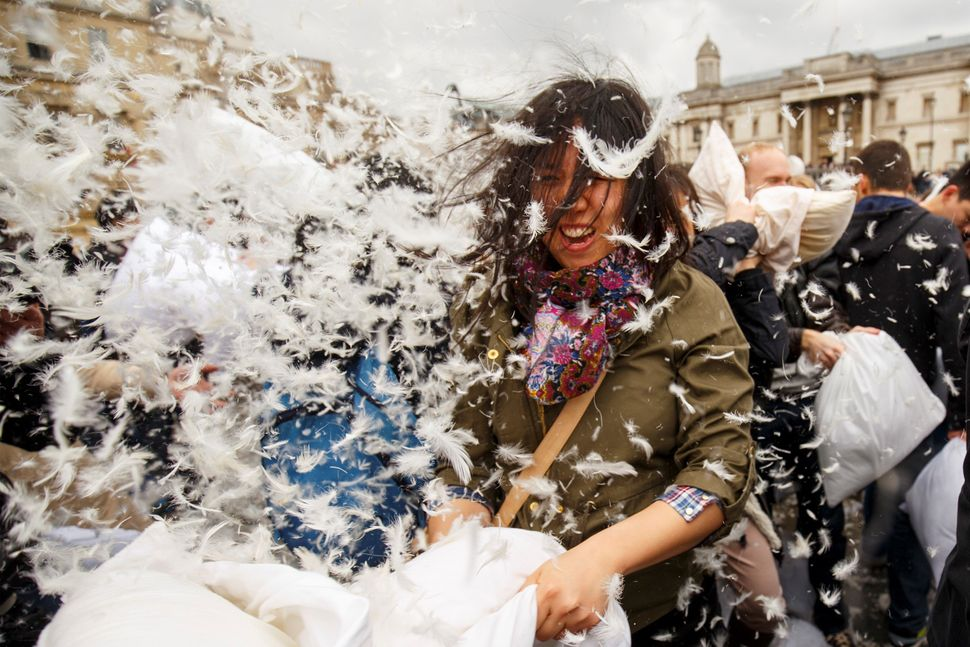 Revelers take part in a giant pillow fight to celebrate International Pillow Fight Day in London's Trafalgar Square on April