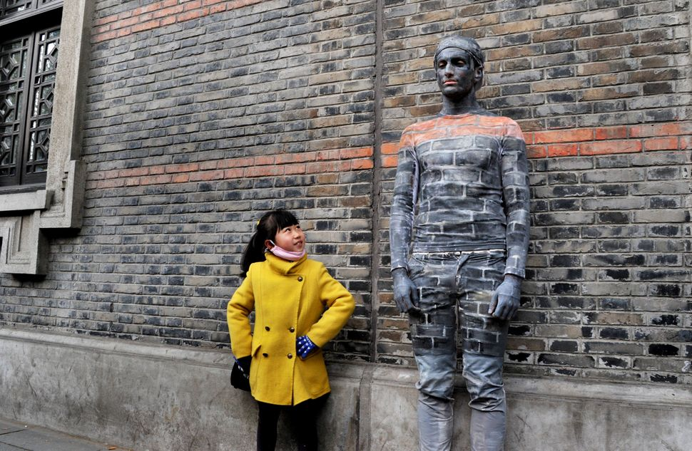 A girl poses with a man disguised as a wall in Shanghai, China, on April 10.