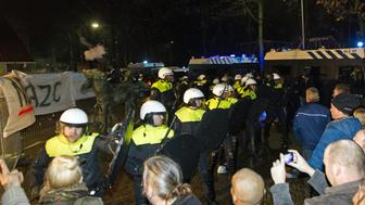 Police forces stand in front of protestors during a demonstration on December 16, 2015 at a council meeting about plans to open a refugee centre for 1500 refugees in  Geldermalsen. / AFP / ANP / Jeroen Jumelet / Netherlands OUT        (Photo credit should read JEROEN JUMELET/AFP/Getty Images)