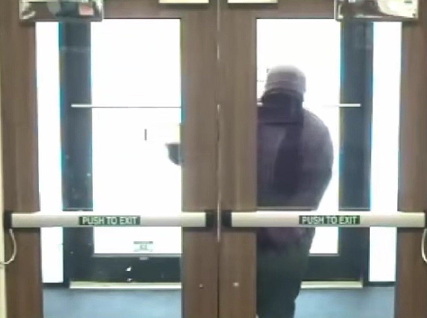 Dumb bank robber has trouble with door.