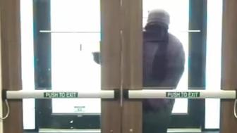 Dumb bank robber has trouble with door.