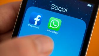 BERLIN, GERMANY - FEBRUARY 25: Facebook next to the WhatsApp logo on iPhone hold by a hand. on February 25, 2014 in Berlin, Germany. (Photo by Marie Waldmann/Photothek via Getty Images)