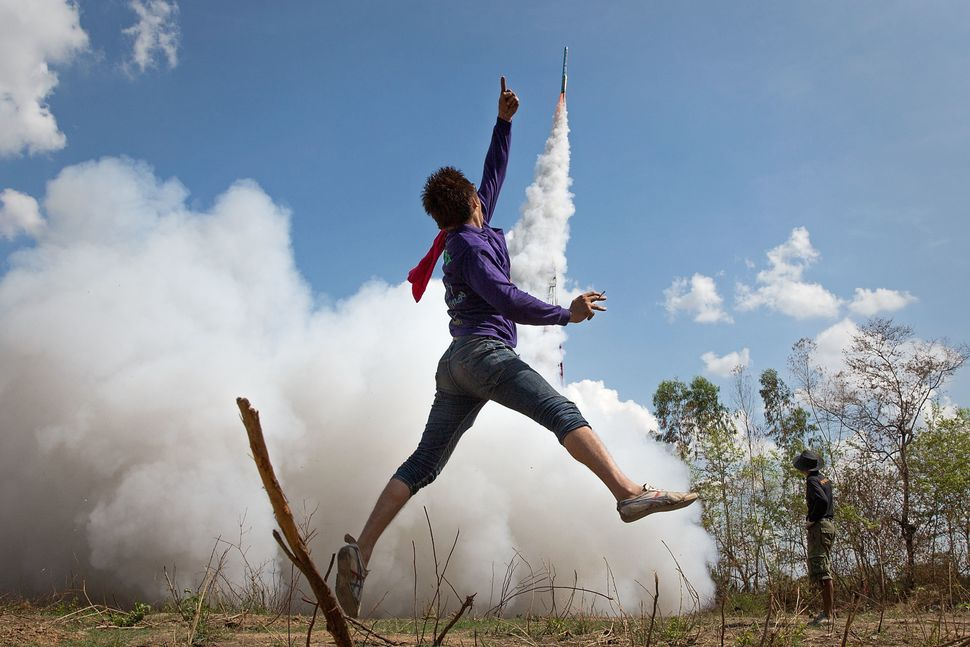 A man cheers as his home-made rocket takes off at the Bun Bang Fai Rocket Festival, marking the beginning of the rainy season