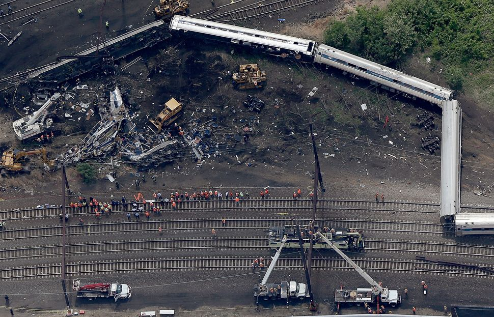 "Investigators work near the wreckage of an Amtrak Northeast Regional train from New York to Washington, D.C., that <a href=""h"