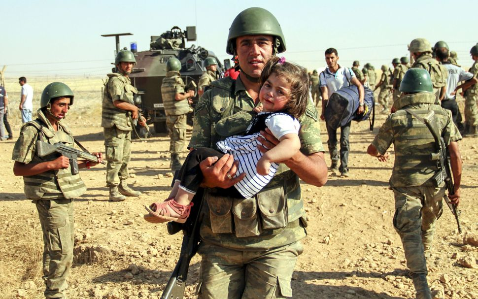 "A Turkish soldier carries a Syrian girl as she enters&nbsp;Turkey at the Akcakale border crossing on June 6. Over <a href=""ht"