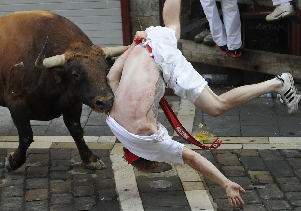 A bull charges at a participant during a bull run at the San Fermin Festival in Pamplona, Spain, on July 7.
