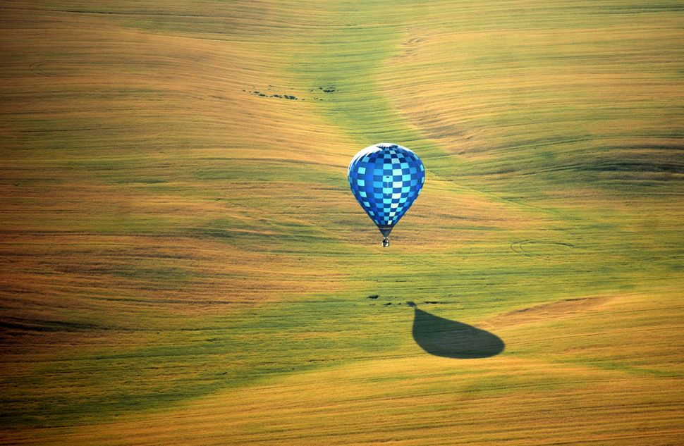A hot air balloon flies over the outskirts of Minsk, Belarus, during the second International Aeronautics Championship on Jul