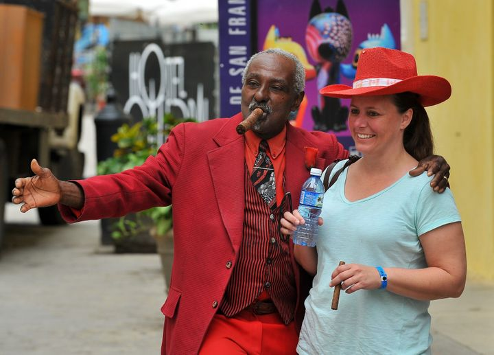 tourist poses with a Cuban man as she visits the Old Havana, on December 16, 2015.