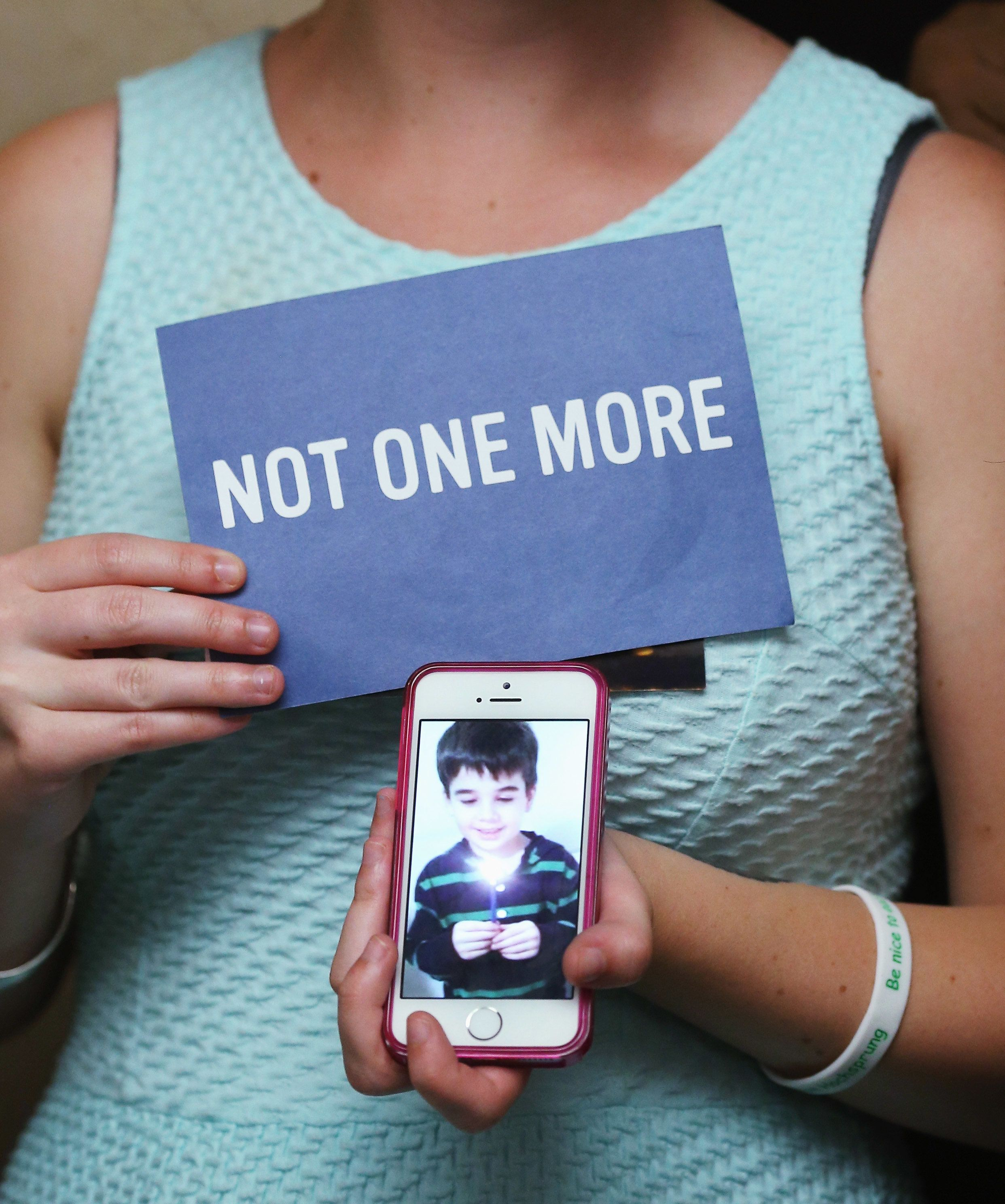 WASHINGTON, DC - JUNE 17: Danielle Vabner holds a image of her little brother Noah Pozner, who was shot and killed in the Newtown Connecticut. massacre, during a news conference on gun safety, on June 17, 2014 in Washington, DC. Family members of gun violence victims announced the ''Not One More' campaign urging Americans to call on Congress to pass better gun safety laws.   Photo by Mark Wilson/Getty Images)  (Photo by Mark Wilson/Getty Images)