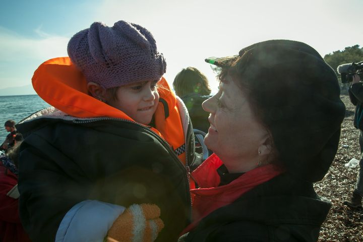 Susan Sarandon greets a 5-year-old Iranian refugee as she arrives on the shore of Lesbos, Greece.