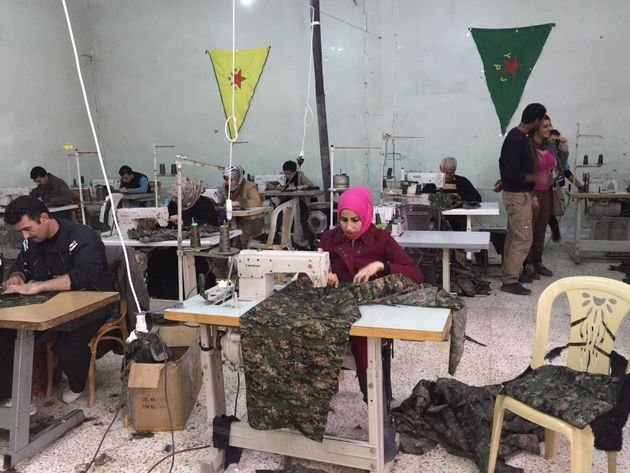 A Rojava sewing cooperative in Derik, Rojava, Syria, in December 2014. Workers are sowing uniforms for...