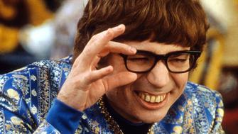 Mike Myers wearing an ornate blue jacket while squinting through his black rimmed glasses in a scene from the film 'Austin Powers: The Spy Who Shagged Me', 1999. (Photo by New Line Cinema/Getty Images)