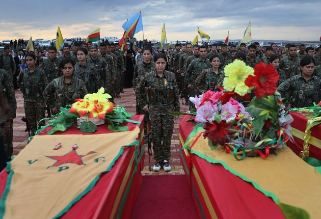 Members of the female division of the Syrian Kurdish militia, the YPJ, take part in the funeral of eight...