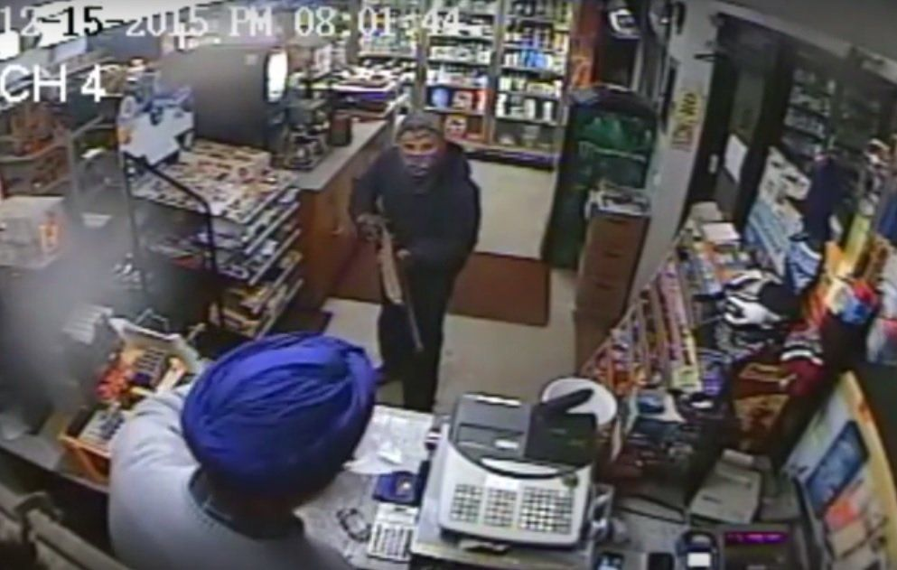 Amrit Singh filling a bag with cash after a masked man wielding a shotgun demanded money