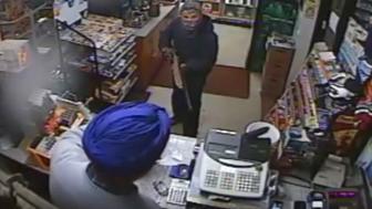Amrit Singh filling a bag with cash after a masked man wielding a shotgun demanded money