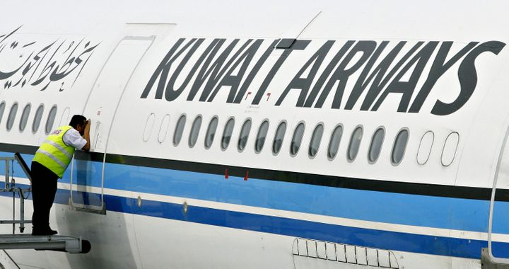 In this file photo from 2006, a crew member peeks inside the cabin of a Kuwait Airways Airbus A340. The airlin