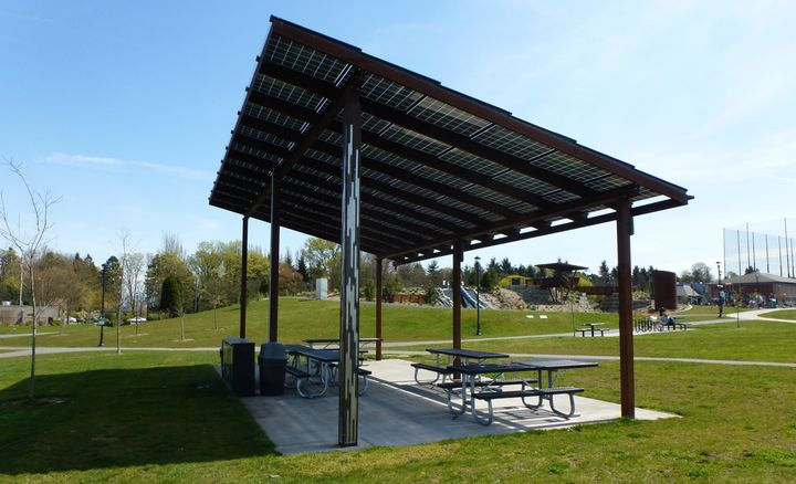 A couple of dozen solar panels sit atop a picnic shelter at a neighborhood park in Seattle.