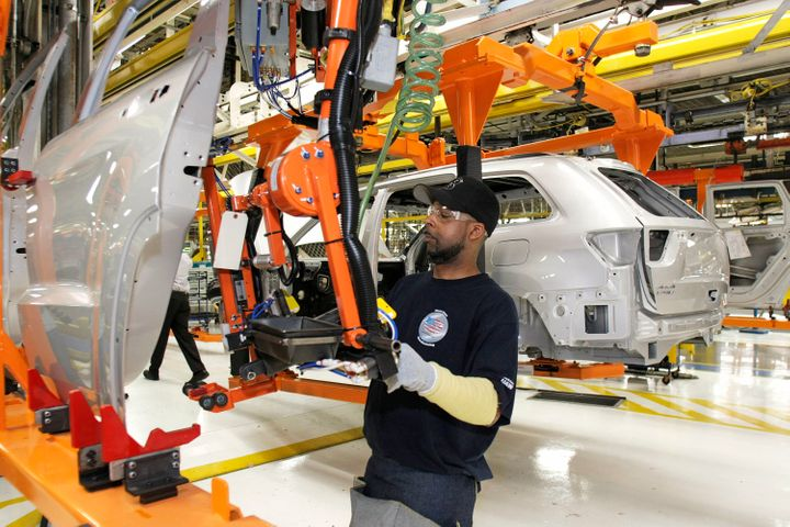 A Chrysler employee works on the assembly line making the new Jeep Grand Cherokee at the Chrysler Jefferson Avenue Plant, May