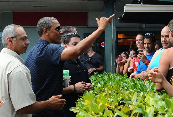 "Obama waves a shaka to a crowd after buying ""shave ice."""