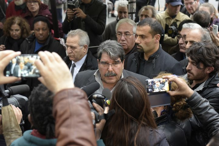 Salih Muslim Muhammad, chairman of the PYD, answers journalists' questions as he arrives to pay tribute to the victims of the