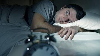 young man in bed with eyes wide opened suffering insomnia , stress and sleep disorder thinking about his problem