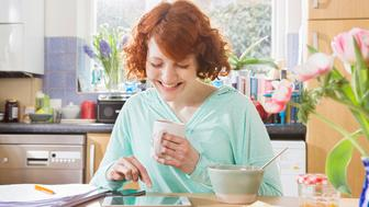 Woman with digital tablet while having breakfast.