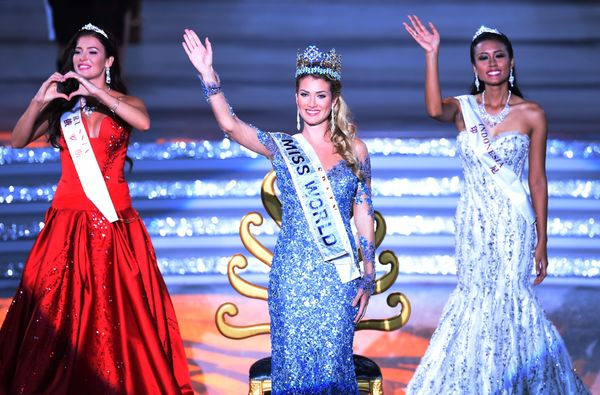 Mireia Lalaguna Rozo (C) of Spain waves after winning the new title at the Miss World Grand Final in Sanya, China, next to Mi